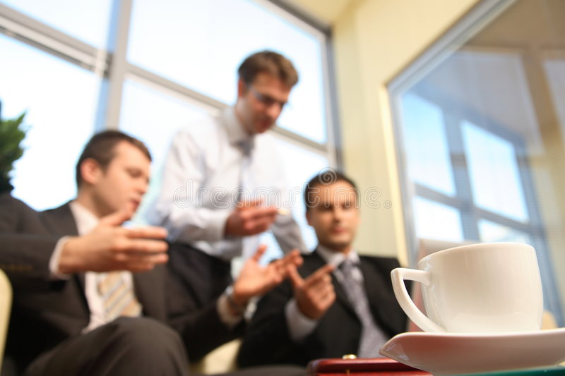 Young business men talking in an office -blur stock images