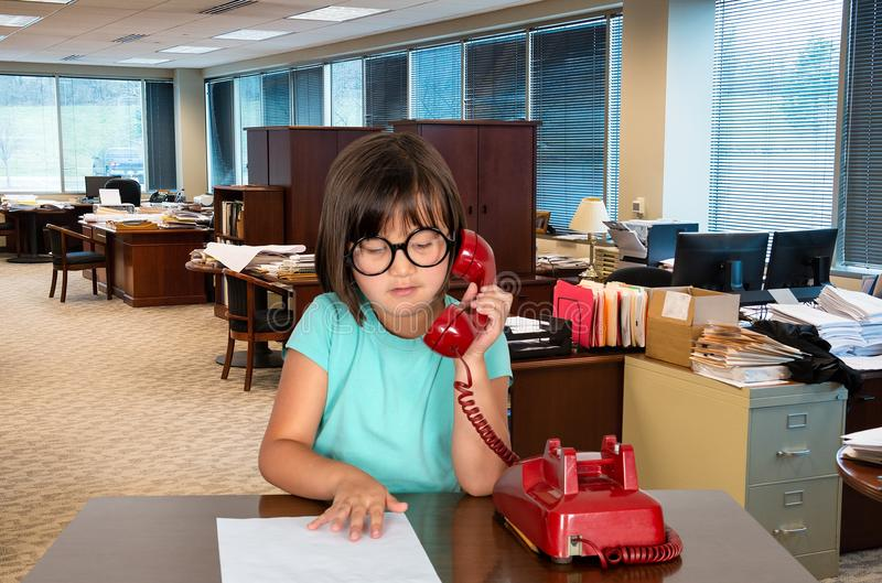 Young Business Office Girl, Worker. A young girl plays in a business office answering a vintage, retro red phone. The child uses her imagination to play work stock photography