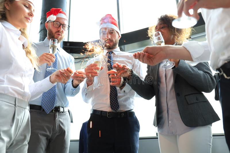 Young business partners are lighting bengal lights and drinking champagne in a modern office. Merry Christmas royalty free stock photo