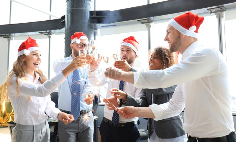 Young business partners are lighting bengal lights and drinking champagne in a modern office. royalty free stock photo