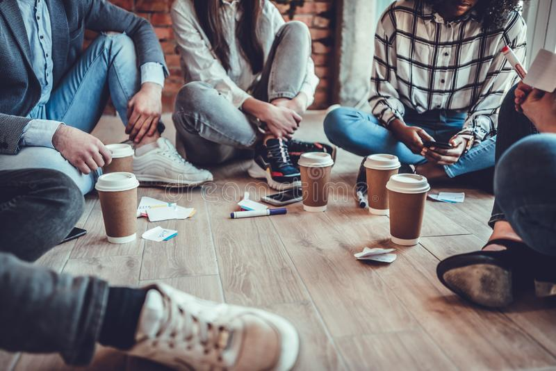young business people in casual clothes are discussing work, drinking coffee and smiling while sitting on the floor in office stock images