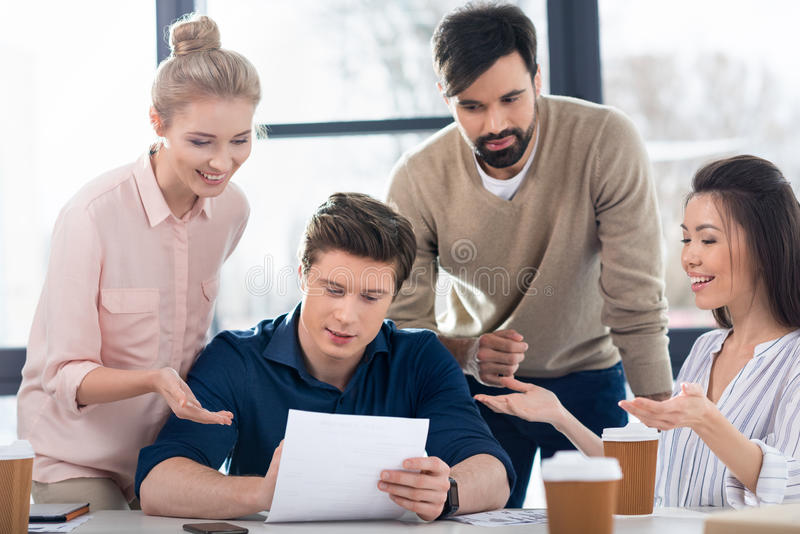 Young business people discussing new project on small business meeting. Group of young business people discussing new project on small business meeting stock image