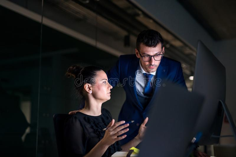 Young business people in an office at night, using computer. stock photo