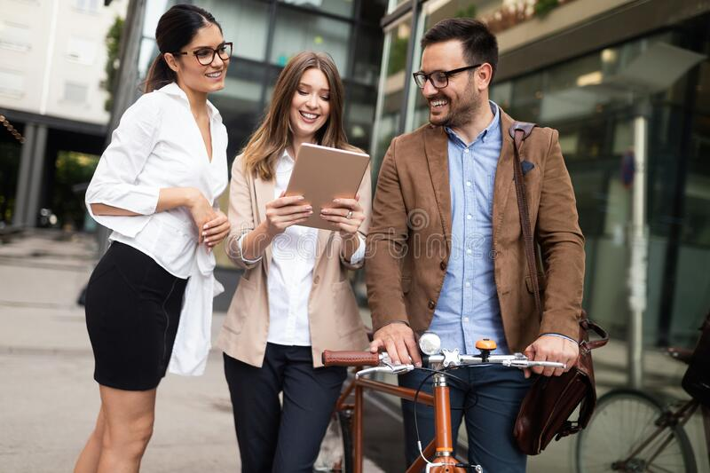 Young business people outdoors working, brainstorming. Technology concept stock image
