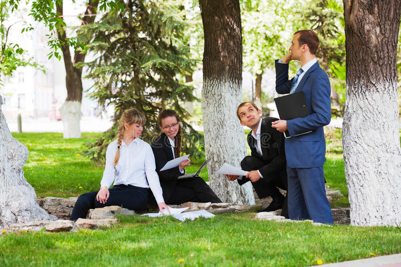 Young business people working in a city park royalty free stock photo