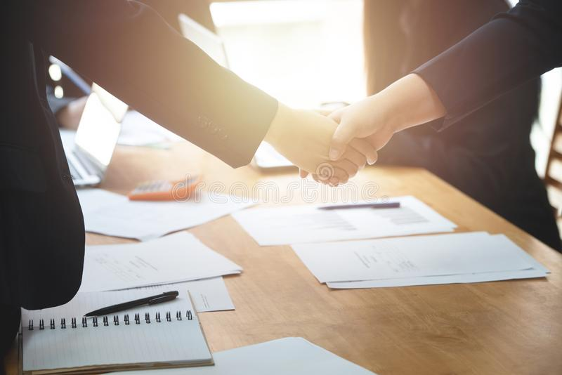 Young business people shaking hands in the office. Finishing successful meeting. Business executives to congratulate the joint royalty free stock photos