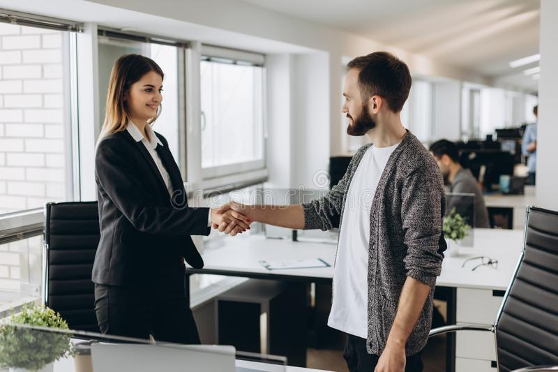 Young business people shaking hands in the office. Finishing successful meeting royalty free stock photos