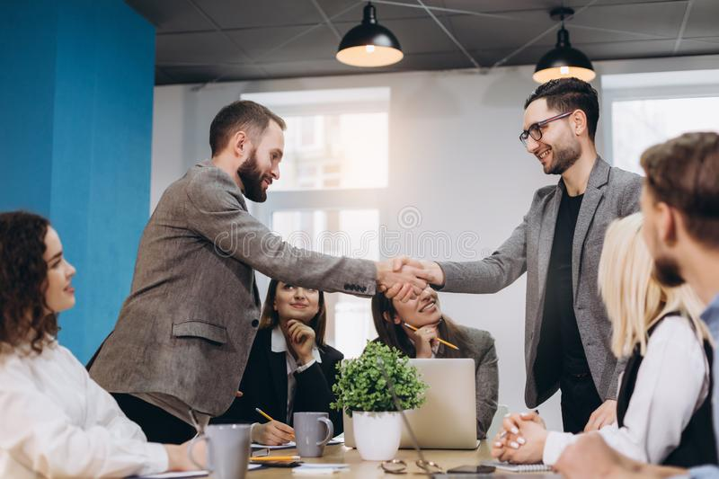 Young business people shaking hands in the office. Finishing successful meeting stock photography