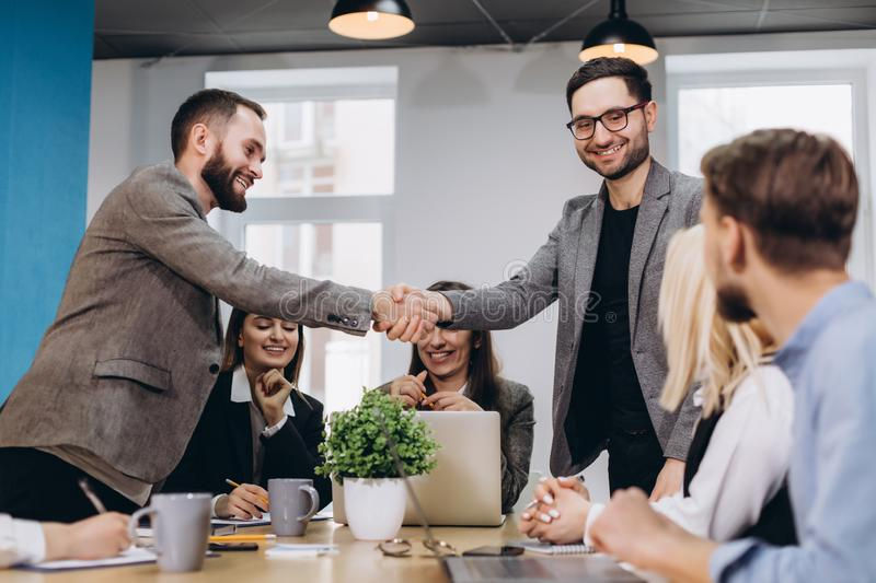 Young business people shaking hands in the office. Finishing successful meeting stock photos