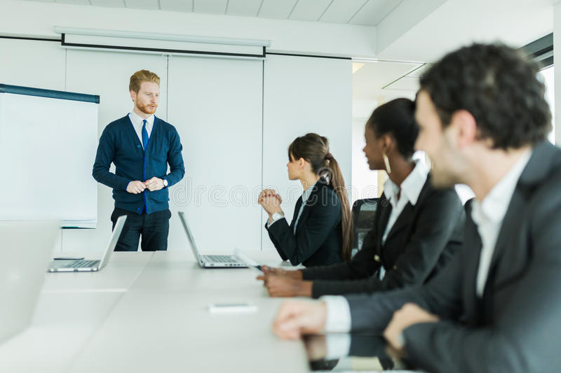 Young business people sitting at a conference table and learning. Young business people sitting at a conference table while listening to the lecturer and royalty free stock photography