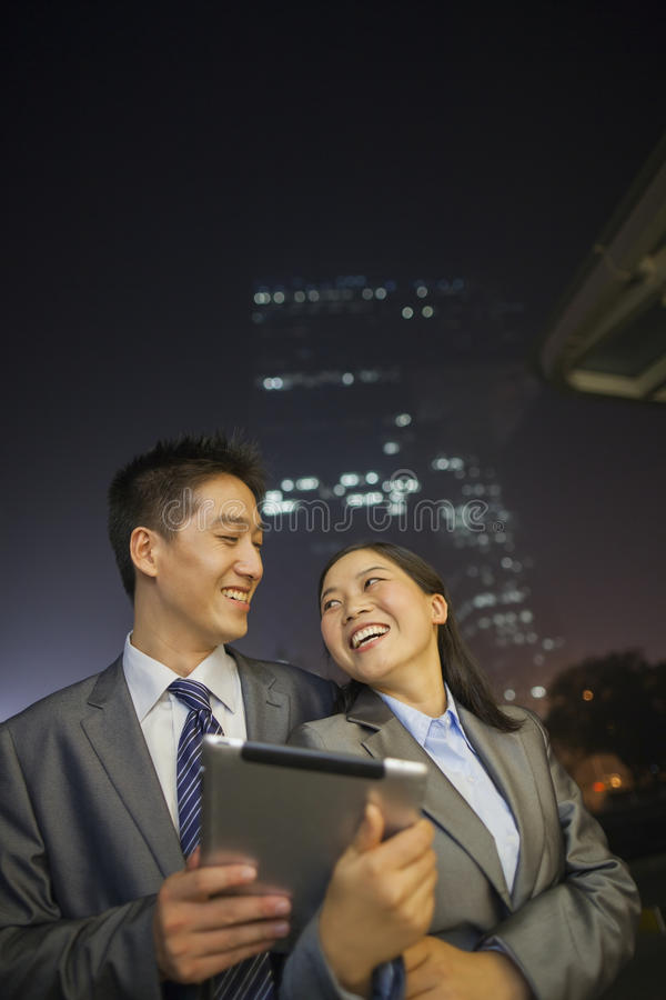 Download Young Business People Smiling And Holding Digital Tablet, Night And Outdoors Stock Image - Image: 31128377