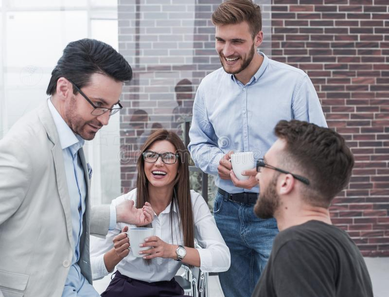 Young business people are talking and smiling during the coffee break in office royalty free stock images