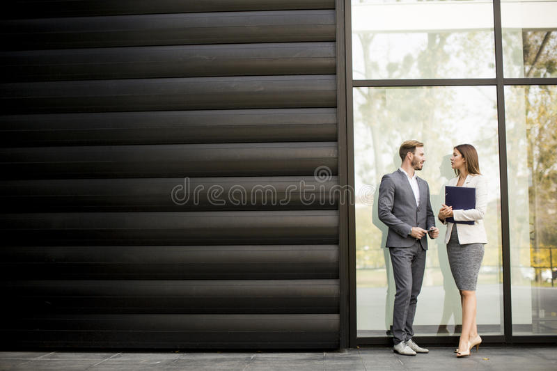 Young business people talking and viewing documents outdoor royalty free stock image