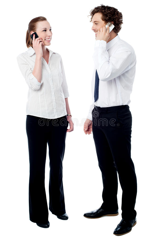 Young business people using cell phones. Business executives talking on the mobile phone royalty free stock photo