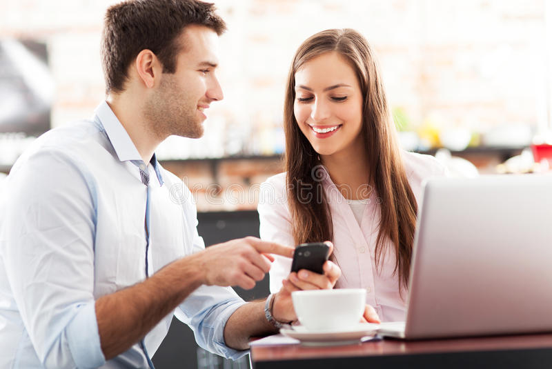 Business people using laptop at cafe royalty free stock photography