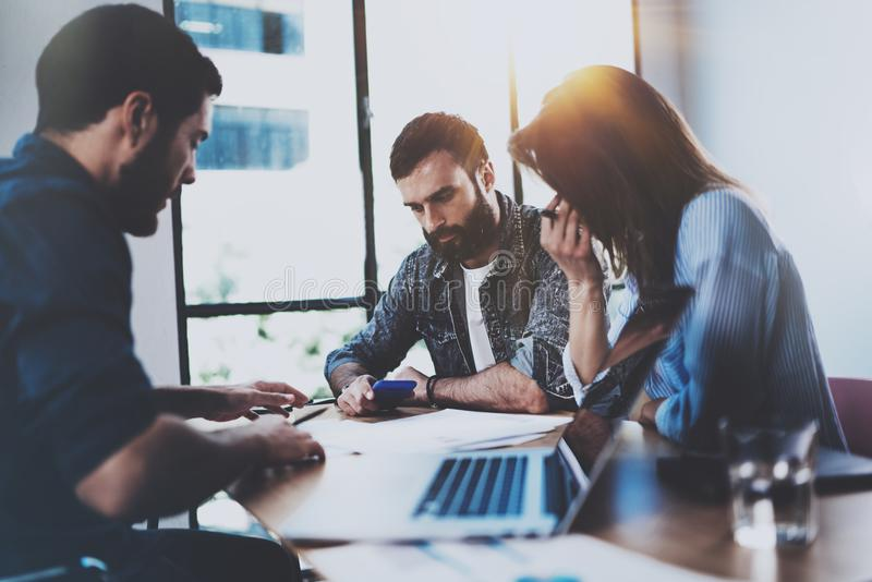 Young business professionals discussing new business project in modern office. Group of three coworkers brainstorming at. Meeting room. Horizontal, blurred royalty free stock images
