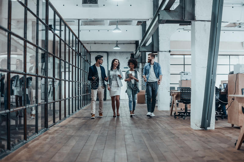 Young business professionals. Full length of young modern people in smart casual wear discussing business while walking through the office corridor stock photos