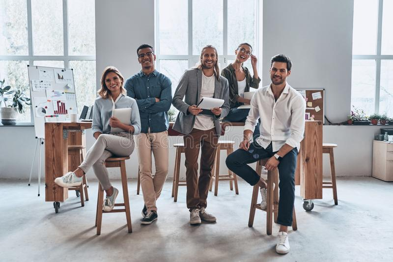 Young business professionals. Full length of young modern people in smart casual wear smiling and looking at camera while standing in the creative office stock image