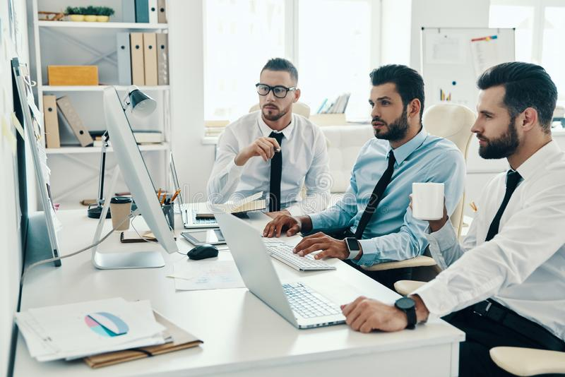 Young business professionals. Group of young modern men in formalwear working using computers while sitting in the office stock photo