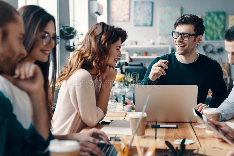 Young business professionals. Group of young modern people in smart casual wear discussing something and smiling while working in the creative office stock images