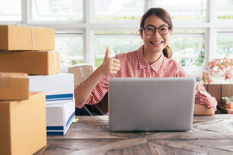 Young business start up online seller owner using computer for checking the customer orders from email or website and preparing royalty free stock image