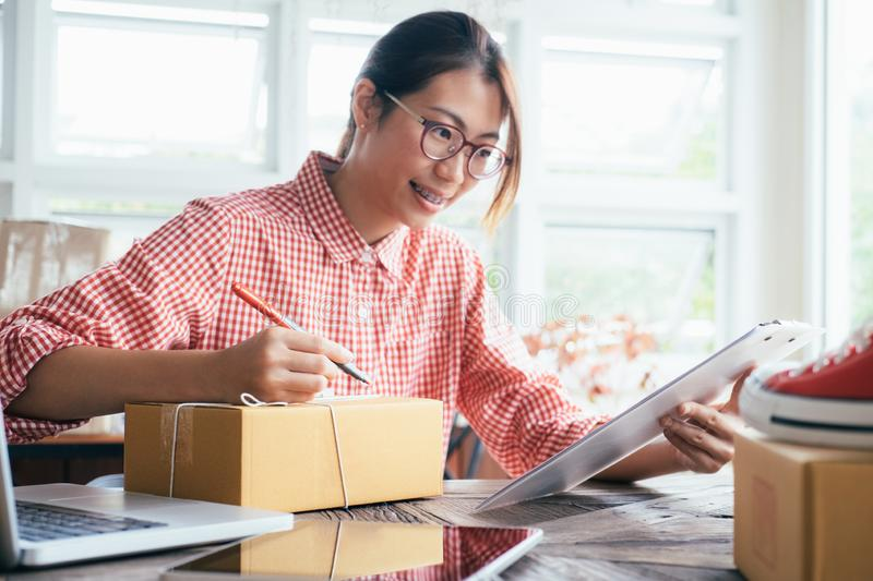 Young business start up online seller owner using computer for checking the customer orders from email or website and preparing royalty free stock photography