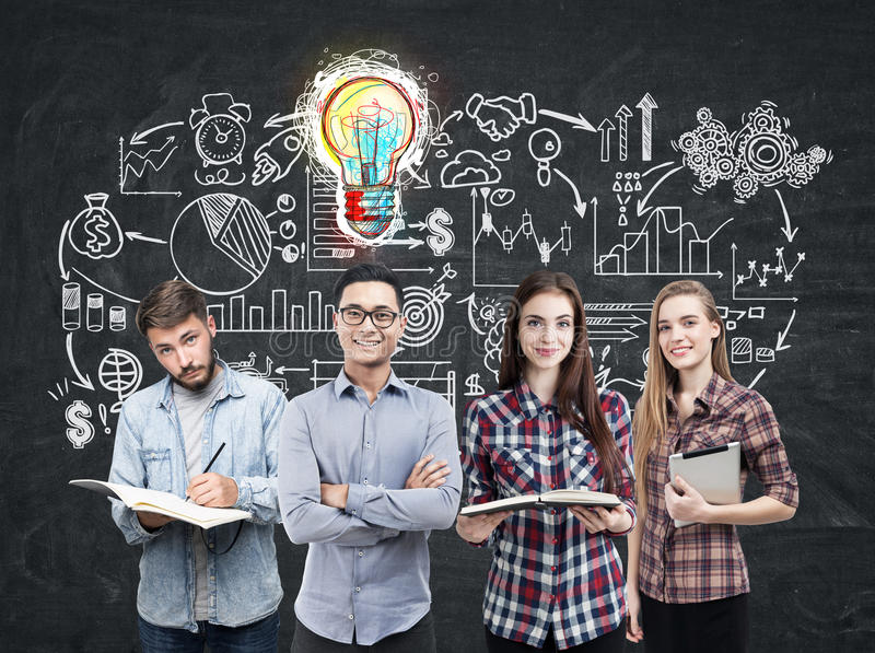 Young business team and bright idea. Portrait of a young business team standing with books and a tablet computer near a blackboard with a bright business idea royalty free stock photos