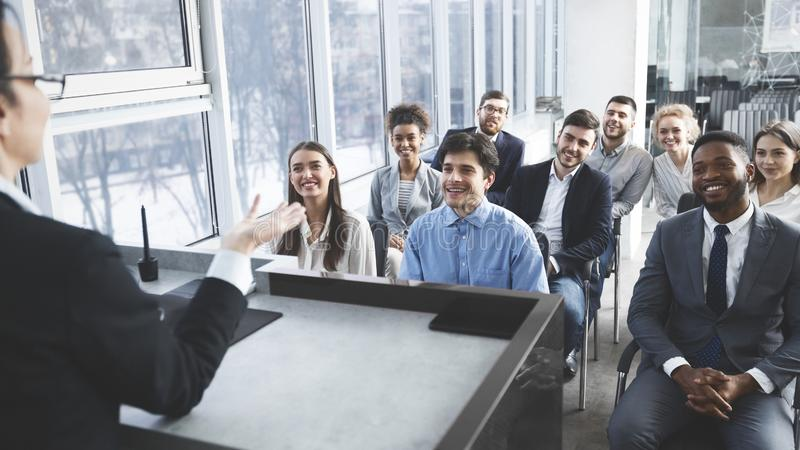 Young business team listening to speaker at meeting stock image