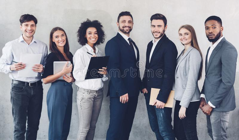 Young business team looking at camera in office. Young business team looking at camera, having break in office, grey background royalty free stock image