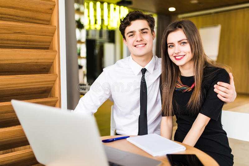 Young business team working together at a laptop smiling as they see their project come to fruition, man and woman. Pleased young business team working together royalty free stock image