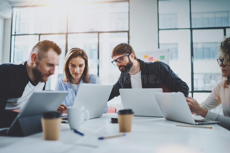 Young business team working together in meeting room at sunny office.Coworkers brainstorming process concept.Horizontal. Blurred background stock image