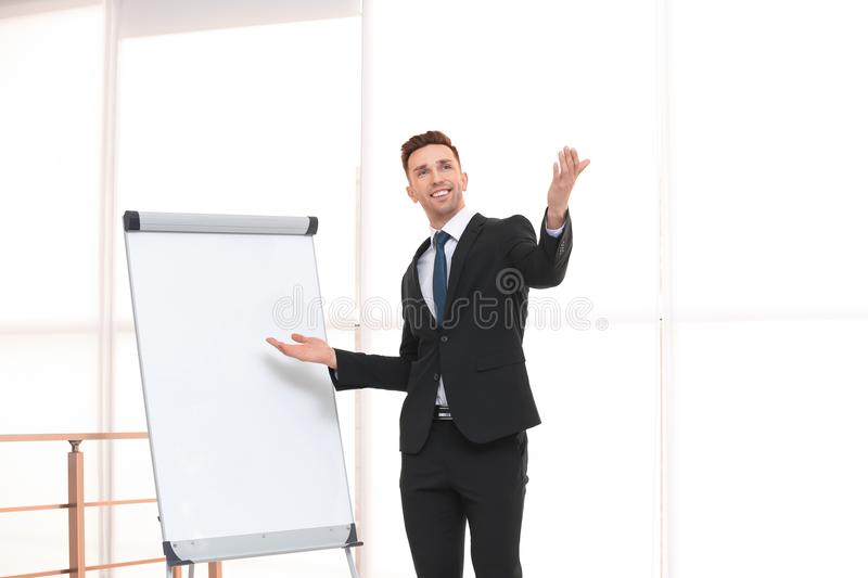 Young business trainer near flip chart royalty free stock image