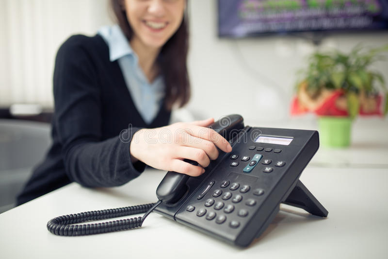 Young business woman answering phone call.Good news.Customer service representative on the phone. Cheerful secretary answering phone in her office.Desk table royalty free stock photos