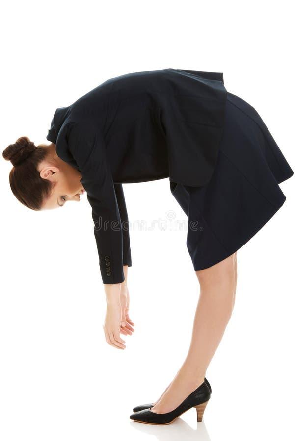Young business woman bending down. stock photos