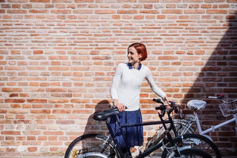 A young business woman with bicycle standing outdoors. Copy space. royalty free stock image