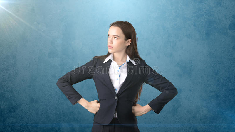 Young business woman in black suit and white shirt is standing, holding her hands on hips. Isolated. Blue background. stock photos