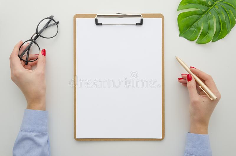 Young woman in blue shirt with a beautiful red manicure holds a pen in her hands and fills the A4 size documents on the royalty free stock photo