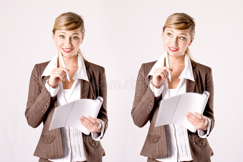 Young business woman with business papers. Young blond business woman with business papers and a ballpen stock image