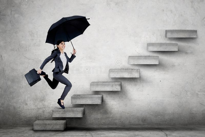 Young business woman running on the staircase stock image