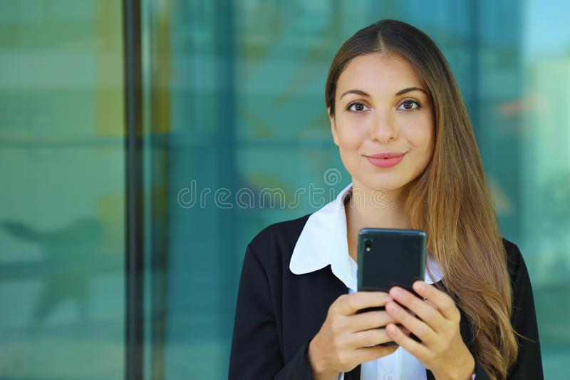 Young business woman checking her smart phone and looking at camera out of office. Copy space royalty free stock photography