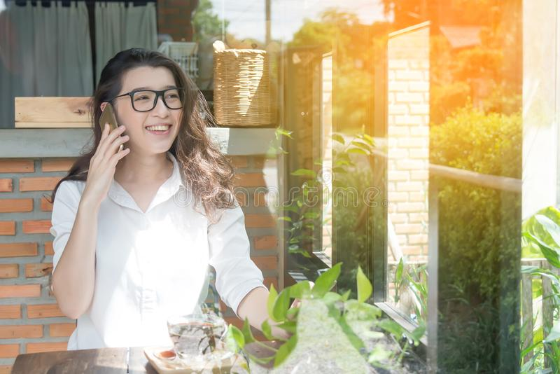 Young business woman cheerful smile sitting at terrace cafe, enjoying online communication using free wireless internet connection. On her Web-enabled smart royalty free stock photo