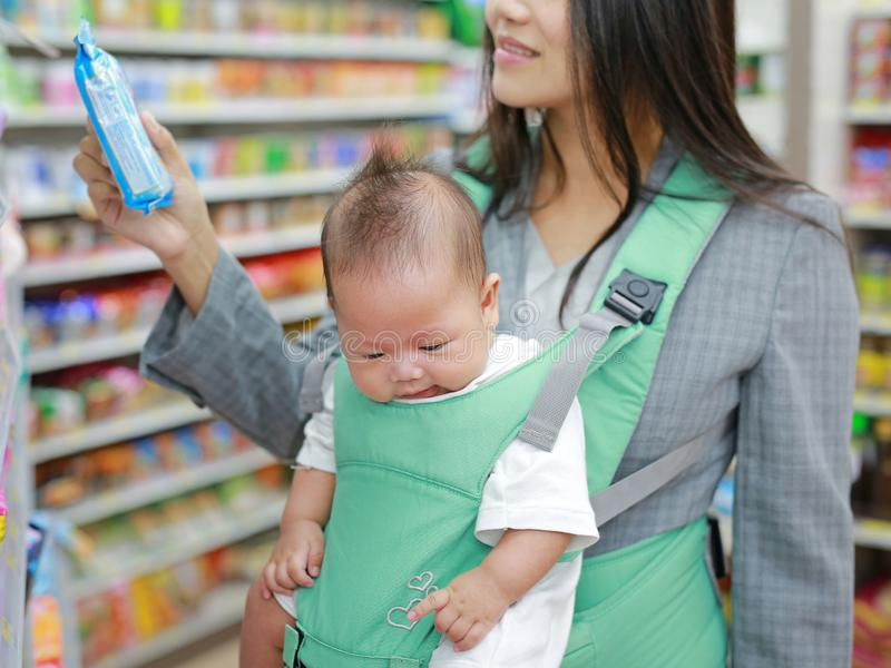 Young business woman in Convenience Store while carrying her baby boy by ergonomic baby carrier royalty free stock photos