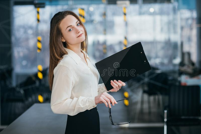 Young business woman corporate executive workplace. Young business woman. Successful corporate executive at workplace. Pretty female holding glasses and folder royalty free stock photos