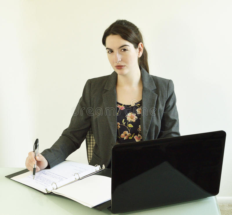 Young Business Woman at Desk with laptop and notebook royalty free stock photos