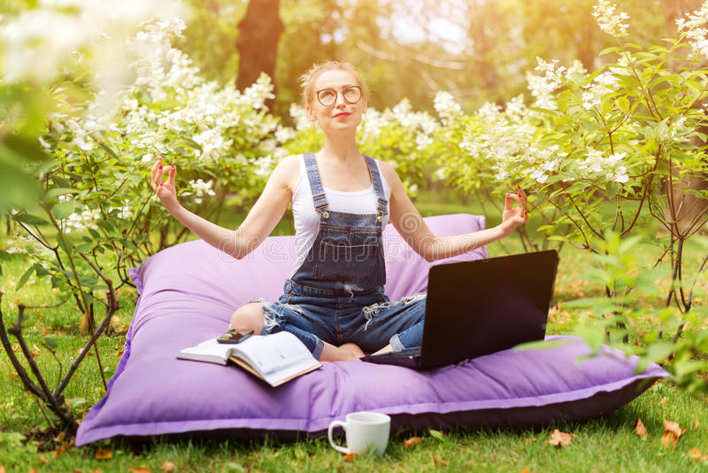 Young business woman doing yoga outside office building sitting in lotus position in the park with her laptop and cup of tea or co royalty free stock photos