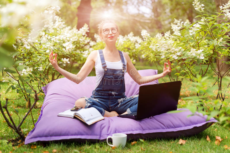 Young business woman doing yoga outside office building sitting in lotus position in the park with her laptop and cup of tea or co royalty free stock photography