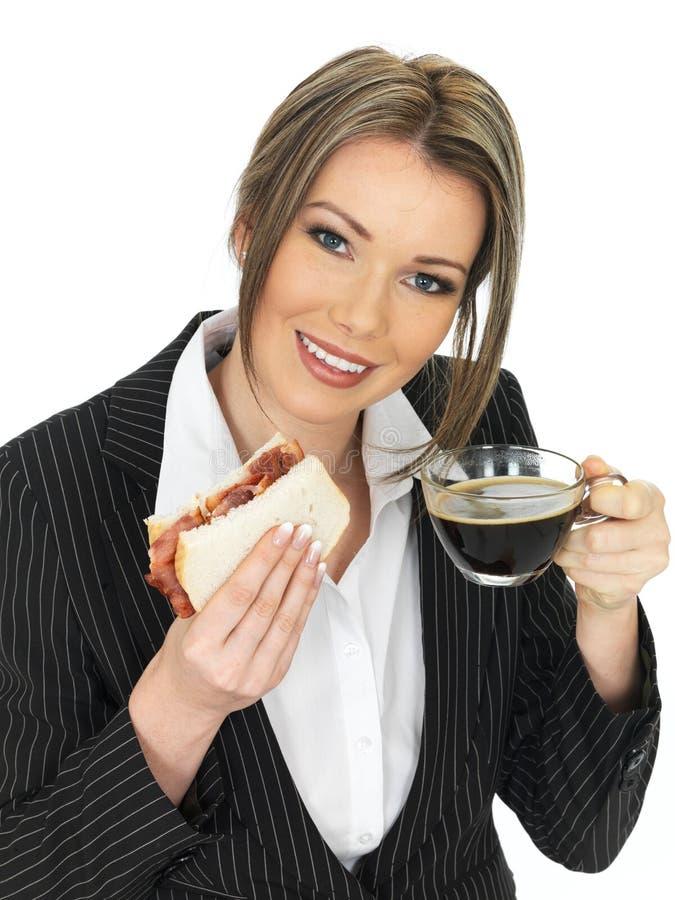 young-business-woman-eating-bacon-sandwi