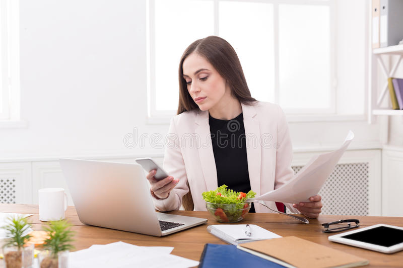 Young business woman eating salad at office royalty free stock images