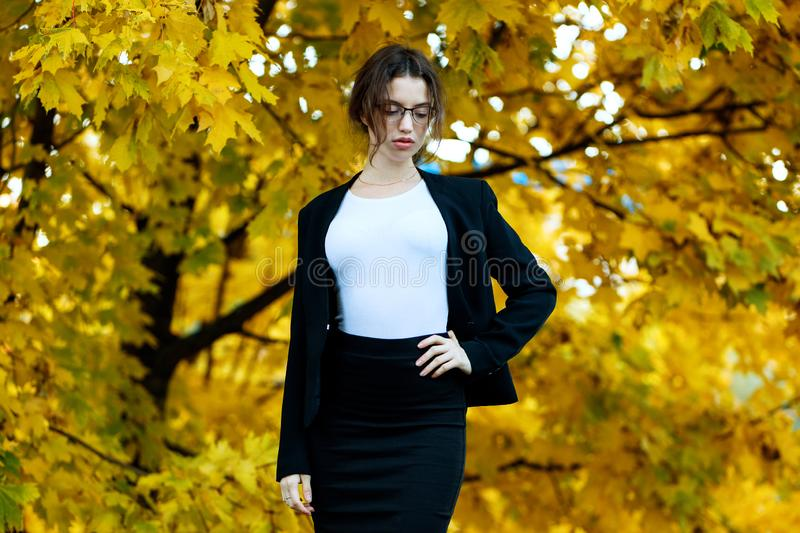 Business woman in formal wear stands over yellow autumn trees. Young business woman in formal wear stands over yellow autumn trees stock image