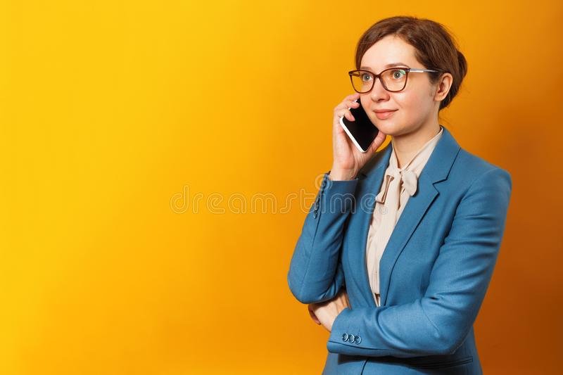 Young business woman in glasses and a suit talking on a cell phone on a yellow background stock image
